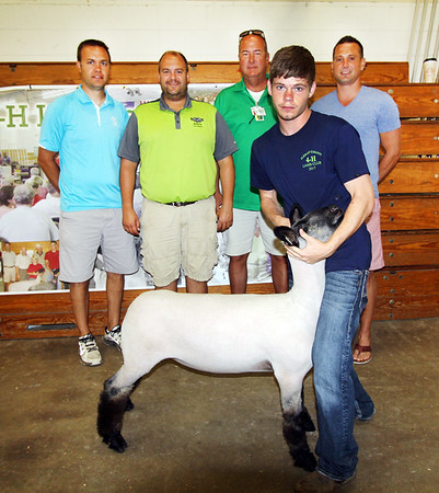 JOHN KLINE | THE GOSHEN NEWS<br /> Grand Champion Lamb winner Austin Bernicky, Claypool, second from right, is shown with his winning lamb and buyers, from left, Troy Wuthrich, Lippert, Brian Lambright, Shipshewana Auction, Tim Graber, Tim Graber Farms, and Ryan Thwaits during the Elkhart County 4-H Lamb Auction Friday afternoon.