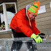 BEN MIKESELL | THE GOSHEN NEWS<br /> Stan Horne of Churubusco smooths out a piece of his ice sculpture Thursday outside of Davis Mercantile in Shipshewana. For this year's festival, the 10-year veteran is making an ice sleigh that people can sit in, which will weigh close to 2,200 pounds.