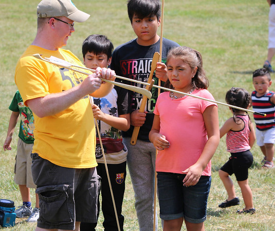 SHERRY VAN ARSDALL | THE GOSHEN NEWS<br /> At left, Patrick McGuire, curator of education at Elkhart County Historical Museum, explains how to throw an atlatl spear during the 50th celebration of Elkhart County Parks at Ox Bow County Park in Dunlap Sunday afternoon.