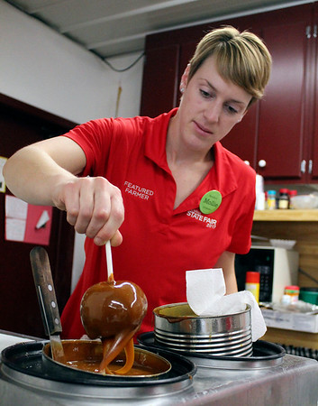 Roger Schneider | The Goshen News<br /> Mollie Kieffer makes a carmel apple Saturday at Kercher's Orchard and Farm Market's Fall Harvest Festival Saturday.