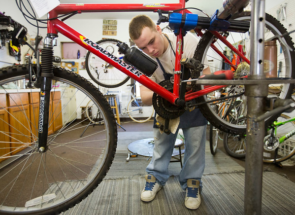 JAY YOUNG   THE GOSHEN NEWS<br /> Matthew Lemons, of Elkhart, cleans and oils the chain on a mountain bike Wednesday morning at Chain Reaction Bicycle Project, 510 East Washington Street. Lemons was at the shop to find a bicycle for himself. The shop allows anyone to work off the price of a bicycle by working in the shop.