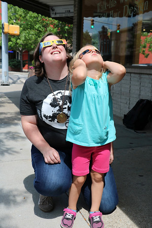 ADAM RANDALL | THE GOSHEN NEWS<br /> Danae Miller and Eliza Bell, 4, Goshen, stand on the sidewalk downtown outside the Nut Shoppe while the eclipse passed over Goshen.