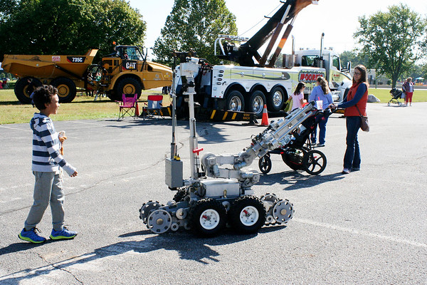 SHEILA SELMAN | THE GOSHEN NEWS<br /> Liam Okponobi, 7, Goshen, follows a robot around the parking lot at Faith United Methodist Church Saturday during Touch-A-Truck.