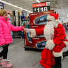 "BEN MIKESELL | THE GOSHEN NEWS<br /> Bob Deveau, dressed as Santa, gives a candy cane to Logan Jenkins, 8, of Goshen on Dec. 13 at the Walmart on Elkhart Road. ""I get down on one knee so I don't scare the kids,"" Deveau explained. ""They seem to be more comfortable when you're at their eye level."""