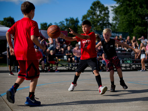 JAY YOUNG | THE GOSHEN NEWS<br /> Nine-year-old Braxton Cline, center, passes the ball to teammate Levi Sawatzky, 9, left, to avoid defender Braxton Wallace, 11, as they compete in the three-on-three basketball tournament Monday evening at the Elkhart County 4-H Fair.