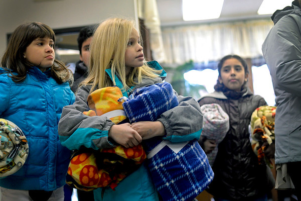 BEN MIKESELL | THE GOSHEN NEWS<br /> Annika Schrock, a fifth-grader at Chamberlain Elementary School, carries fleece blankets Tuesday into The Window. Chamberlain students made 75 fleece blankets to be delivered as part of Mayor Jeremy Stutsman's Year of Goodness initiative.