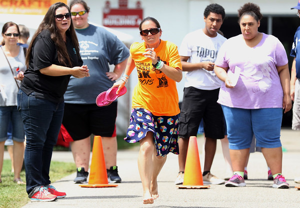 JAY YOUNG | THE GOSHEN NEWS<br /> [NEED NAME FROM LEANDRA] takes off her flip-flops to race down the sidewalk at the 10-meter dash skills event during Disabilities Awareness Day at the Elkhart County 4-H Fair Monday afternoon.