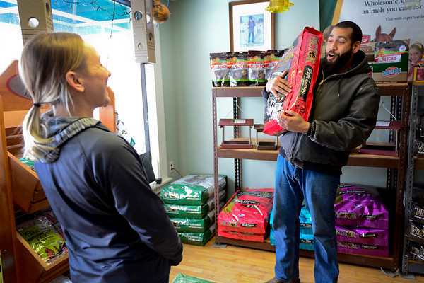 BEN MIKESELL | THE GOSHEN NEWS<br /> While picking up dog food, Elliot Moore of Goshen talks with Jessica Watson Thursday inside Jack's Feed Shack in Bristol. Weeks ago, Moore's mother told Watson about a book she wanted her son to get her for Christmas, so Moore purchased it.