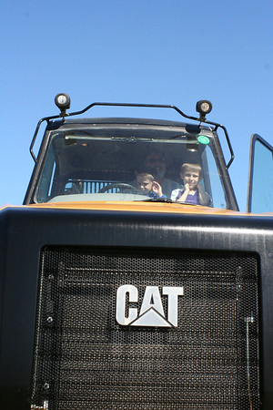 SHEILA SELMAN | THE GOSHEN NEWS<br /> Kurt Vogel and his two sons, Trevor, 9, and Kevin, 7, all of Elkhart, enjoy sitting in a large Caterpillar tractor at Touch-A-Truck Saturday at Faith United Methodist Church near Goshen.