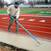 BEN MIKESELL | THE GOSHEN NEWS Tim Denlinger of Goshen smooths out a concrete sidewalk Monday afternoon at Goshen High School's Foreman Field, prior to the installation of the field's new bleachers. His family's business, J.L. Denlinger Concrete, spent the afternoon flattening and grooving lines in the new sidewalk. The $900,000 replacement plan for the bleachers was approved in August, and is slated to be complete in the spring.