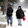 BEN MIKESELL | THE GOSHEN NEWS <br /> Devon White of Goshen, left, walks with his mother Angie to The Window early Thursday morning in downtown Goshen. Thursday's snowfall was the first of the winter season.