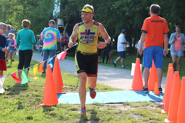 SHERRY VAN ARSDALL | THE GOSHEN NEWS<br /> Gene Cruisie, of Elkhart,  crosses the finish line duirng the third annual Fidler Pond's triathlon and mile swim in Goshen Saturday.
