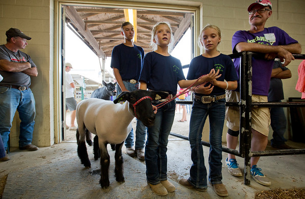 JAY YOUNG | THE GOSHEN NEWS<br /> Nine-year-old Janissa Lehman, of Topeka, center, keeps her goat close while she and her friend Sage Granberg, 10, of Middlebury, wait to enter the beef arena to be recognized during the parade of champions Thursday evening at the Elkhart County 4-H Fair.