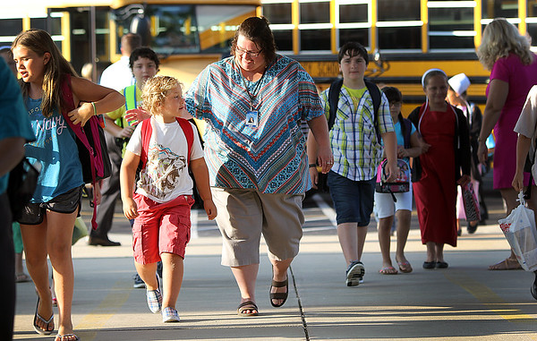 JULIE CROTHERS BEER | THE GOSHEN NEWS<br /> Tina Newcomer, a staff member at Nappanee Elementary School, greets first-grader Elijah Mast as he walks from the bus Wednesday on the first day of school.