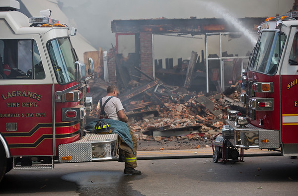 JAY YOUNG | THE GOSHEN NEWS<br /> A firefighter gets a front row seat as he takes a break while helping battle a large fire in downtown LaGrange Tuesday afternoon.