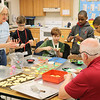 JOHN KLINE | THE GOSHEN NEWS<br /> Cheryl Mast, coordinator of outdoor/environmental education for the Amigo Centre and co-sponsor of the Goshen Middle School E3 Survival Skills for Life program, left, decorates cookies baked by E3 seventh-graders during a holiday cookie-baking service project at the school Friday afternoon.
