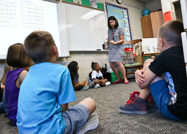 LEANDRA BEABOUT | THE GOSHEN NEWS<br /> On the first day of school at Ox Bow Elementary School, first grade teacher Beth Signor explains her reward system of earning smiley faces or frowns on the board.