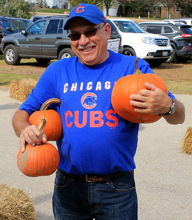 Roger Schneider   The Goshen News<br /> Rany Hughes of Wakarusa had his hands full of pumpkins Saturday at Kercher's Sunrise Orchard and Farm Market.