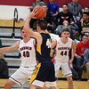 GREG KEIM | THE GOSHEN NEWS<br /> Senior Caleb Goeglein of the Fairfield Falcons looks to pass the ball in a high school boys basketball game Saturday night at Goshen. Guarding him on the play are junior Ben Bontrager-Singer and classmate Bryant Robinson of the hometown RedHawks. The RedHawks were 44-43 winners on a last-second 3-pointer by Robinson.