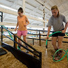 JAY YOUNG | THE GOSHEN NEWS<br /> Jenifer Robinson, 14, hoses down sawdust bedding while her older sister Alison, 16, both of Middlebury, stomps around to pack it down as they prepare a stall for their cattle while getting ready for the county fair Thursday morning.