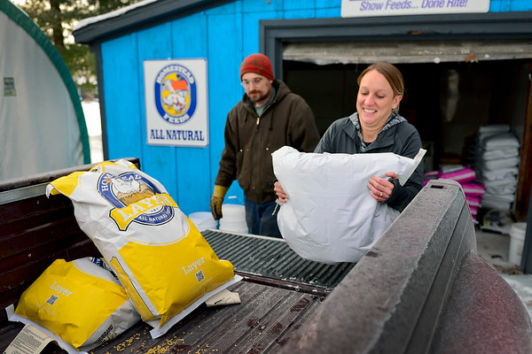 BEN MIKESELL | THE GOSHEN NEWS<br /> Jack's Feed Shack owner Jessica Watson helps put chicken feed in the bed of Alan Cundiff's truck Thursday before he drives back to Scott. Though she's five months pregnant, she insists on helping lift bags as much as she can, but some customers don't let her.