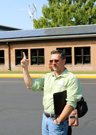JOHN KLINE | THE GOSHEN NEWS<br /> Calvin Swartzendruber, a chemistry and physics teacher at Bethany Christian Schools, points to a section of the school's 300-panel solar array during a tour of the school's sustainability efforts Friday afternoon.