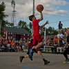 JAY YOUNG | THE GOSHEN NEWS<br /> Nine-year-old Levi Sawatzky hangs in the air to get off a shot over defender Tre Willard, 10, as they compete in the three-on-three basketball tournament Monday evening at the Elkhart County 4-H Fair.