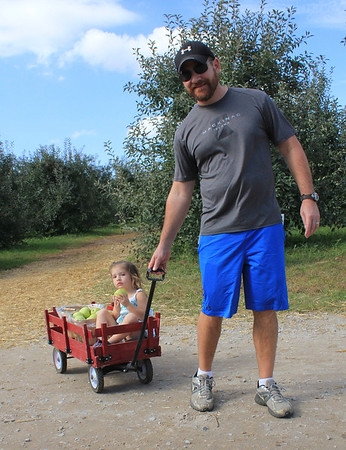 Roger Schneider | The Goshen News<br /> Jason Hill of Wakarusa pulls his daughter Ashlyn, 2, while she eats an apple. They were at the fall festival Saturday at Kercher's Sunrise Orchard and Farm Market in Goshen.