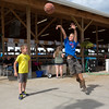 JAY YOUNG | THE GOSHEN NEWS<br /> Nine-year-old Lane Brenneman, of Elkhart, launches a shot while playing basketball at a goal just outside of the cattle stalls Monday afternoon at the Elkhart County 4-H Fair.