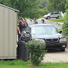 ROGER SCHNEIDER | THE GOSHEN NEWS<br /> Goshen police stand in front of the home where they believe a stabbing occurred at Brookside Manor mobile home park Thursday.
