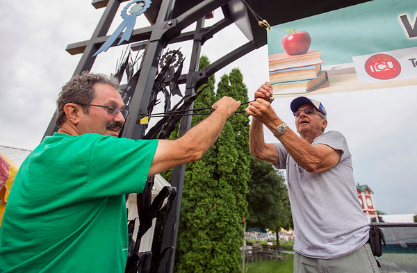 JAY YOUNG   THE GOSHEN NEWS <br /> Sam Perri, left, and Eldie Troyer hang signs at the entrance of  Heritage Park Thursday morning at the Elkhart County 4-H Fairgrounds in preparation for the start of the county fair Friday.