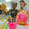 JAY YOUNG | THE GOSHEN NEWS<br /> Karina Kern watches as 7-year-old Bervalie Lehman uses orange and pink paint to color a balloon wrapped in newspaper as they create a piñata during the Bright Time summer camp at Bethany Christian Tuesday afternoon.