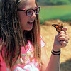 Roger Schneider | The Goshen News<br /> Kirstin Stutzman, 11, Middlebury, watches as a monarch butterfly lands on her had at the feed-the-butterflies attraction at the LaGrange County 4-H Fair Saturday.
