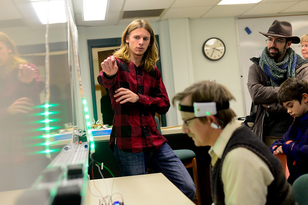 BEN MIKESELL   THE GOSHEN NEWS<br /> Alex Steiner, junior at Goshen College, explains how the mind-controlled robot works as mathematics professor David Housman tests it out Monday at Goshen College's 2017 Electronics & Robotics Show. The headband around Housman's head measures concentration and sends signals for the robot to move along the floor.