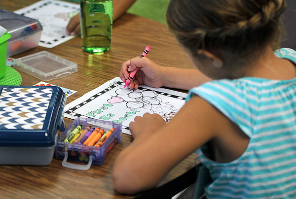 "JULIE CROTHERS BEER | THE GOSHEN NEWS<br /> A first-grade student in Tammy Miller's class at Nappanee Elementary School works on a coloring page with the words ""First is best!"" as students settle in for the first day of school Wednesday."
