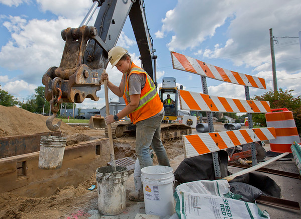 JAY YOUNG | THE GOSHEN NEWS<br /> Morgan Eggleston, with HRP Construction, pours and mixes concrete as work continues on Pike Street in Goshen. Today crews were installing storm water drainage pipes. The work is part of the U.S. 33 realignment project.