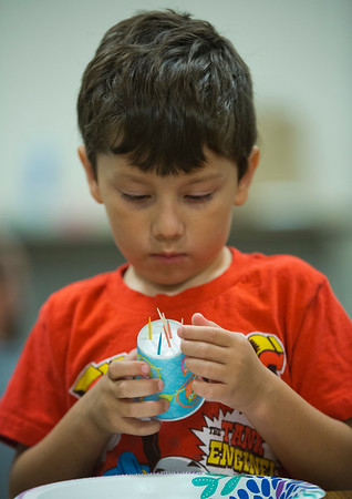 JAY YOUNG | THE GOSHEN NEWS<br /> Five-year-old Lucas Garcia, of Middlebury, pushes toothpicks through a paper cup as he tries to build a house that will withstand the wind Monday afternoon at the Middlebury Community Library. Children spent the afternoon building small houses out of toothpicks, plastic drinking straws and then Legos while they learned the story of the three little pigs. After each house was built, the children would then blow them over like the wolf in the story. Since the Lego houses were so sturdy, they used a parachute, moving it quickly up and down, to generate enough wind to topple the structures.