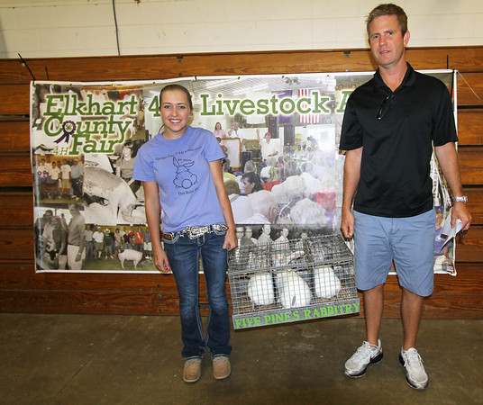 JOHN KLINE | THE GOSHEN NEWS<br /> Grand Champion Rabbit Meatpen winner Brenna White, Goshen, left, is shown with her winning rabbits and buyer Shane Tom of Turtle Top and Associates and Independent Lighting Protection during the Elkhart County 4-H Rabbit Auction Friday afternoon.