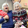 BEN MIKESELL | THE GOSHEN NEWS<br /> Dorothy Landon of Bristol, right, celebrates her 100th birthday by smearing whipped cream from her cupcake on Major Sally Sell's nose Thursday at the Salvation Army in Goshen. Landon turns 100 on Dec. 12, but family and friends celebrated a week early.