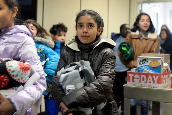 BEN MIKESELL | THE GOSHEN NEWS<br /> Ana Ochoa, a fifth-grader at Chamberlain Elementary School, carries fleece blankets Tuesday into The Salvation Army. Chamberlain students made 75 fleece blankets to be delivered as part of Mayor Jeremy Stutsman's Year of Goodness initiative.