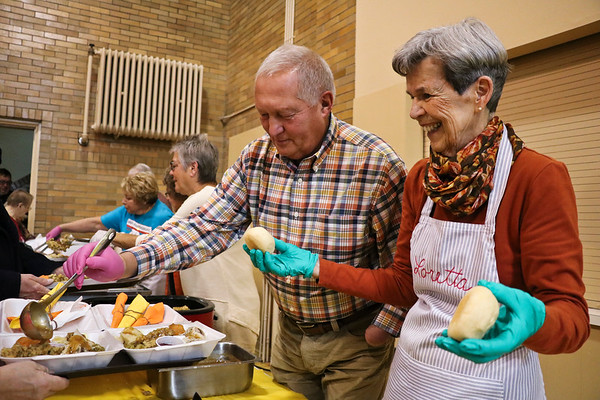 LEANDRA BEABOUT | THE GOSHEN NEWS<br /> Bruce Klonowski of Middlebury and Loretta Reynolds of GOshen dish out to-go Thanksgiving meals.