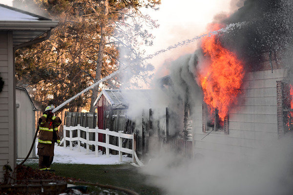BEN MIKESELL | THE GOSHEN NEWS<br /> A fire figher from the Elkhart Township Fire Department sprays down the side of a house fire Tuesday morning on the 16000 block of C.R. 40 in Goshen. The fire started in the garage and quickly spread to the rest of the house, and passersby helped the residents escape safely.