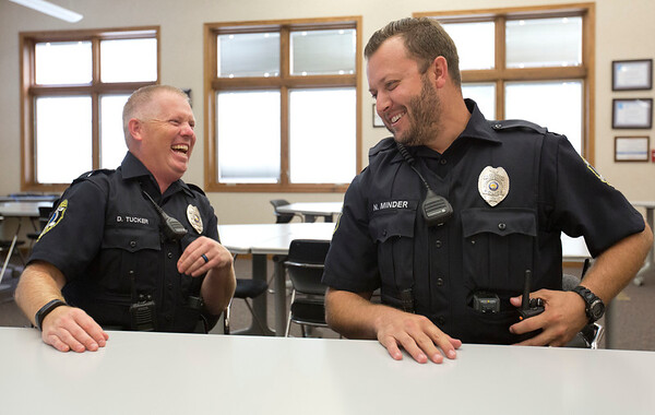 JAY YOUNG | THE GOSHEN NEWS<br /> Concord police officers Darrin Tucker, left, and  Nic Minder share a laugh as they talk about their first week on the job Thursday afternoon at Concord High School. The Concord School District recently incorporated a new police department.