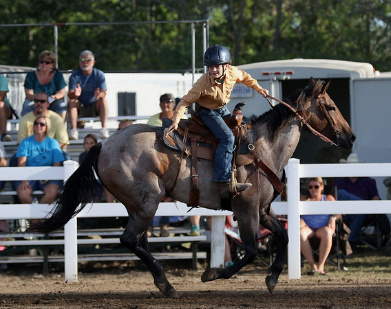 JAY YOUNG | THE GOSHEN NEWS<br /> Coulter Rawlings looks back after dropping a flag in a bucket while riding his horse Skye as he competes in a skills event hosted by the saddle club Tuesday evening at the Elkhart County 4-H Fair.