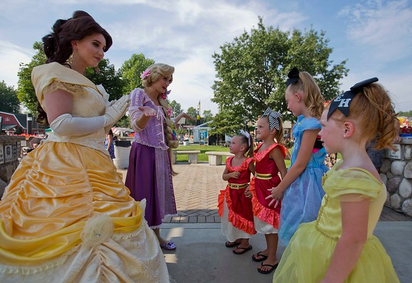 JAY YOUNG | THE GOSHEN NEWS<br /> Belle and Rapunzel, actors from Your Party Princess, meet mini princesses Remi Stichter, 3, of Goshen, Skylie Stichter, 6, of Goshen, Caydence Moon, 8, of Goshen, and Eliannna Smith, of Middlebury, Friday at the Elkhart County 4-H Fair.