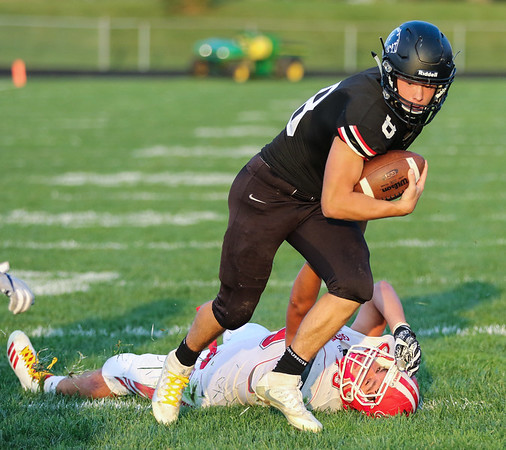 CHAD WEAVER | THE GOSHEN NEWS<br /> NorthWood quarterback Landen Gessinger breaks free from Goshen defensive end Will Koshmider during the first quarter of Friday night's game at NorthWood.