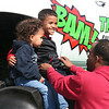 SHEILA SELMAN | THE GOSHEN NEWS<br /> Milam Cook, 5, right, and brother Levi Cook, 3, Elkhart, are put on top of the wheel of a monster truck by dad Marco Cook for photos Saturday during Touch-A-Truck.