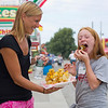 JAY YOUNG | THE GOSHEN NEWS<br /> Ten-year-old Jalyn Stofleth gets a little help from her mother Kristen, both of Goshen, as she tries out the Saratoga chips during Taste of the Fair Thursday evening. Saratoga chips are made from one entire potato that is spiraled and then topped with cheddar cheese, bacon bits and chives. The pair agreed that that despite having never seen anything like it before, the chips were delicious. Taste of the Fair is an annual event taking place the night before the Elkhart County 4-H Fair opens. Fair board president Jill Garris said it is a way to say thank you to the sponsors by letting them and their families come out and sample some of the fair food for free and explore the grounds. Types of food available included a fried enchilada funnel cake, circus peanuts, corn dogs and, of course the Saratoga chips.