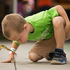 JAY YOUNG | THE GOSHEN NEWS<br /> Four-year-old Zane Trovatore, of Goshen, coaxes his frog to jump by blowing on its back during the frog jump contest Wednesday Morning during Kids' Day activities at the Elkhart County 4-H Fair.
