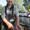 Roger Schneider | The Goshen News<br /> Madelyn Boyer, an intern biologist with the city of Elkhart, holds a chestnut lamprey that was attached to a brown trout that was captured during the Middlebury Riverfest. Fifteen species of fish were captured by electroshocking in the Little Elkhart River and then put on display to educate the public.